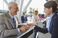 Customer service representative helping businessman at airport check-in counter - CAIF10316