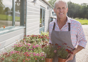 Portrait smiling plant nursery owner with potted flowers - CAIF10328