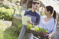 Plant nursery owners with clipboard and potted plants - CAIF10331