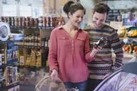 Couple looking at jar in market - CAIF10379