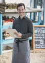 Portrait smiling farmerís market worker with clipboard - CAIF10394