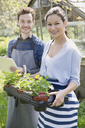 Portrait smiling plant nursery workers with clipboard and potted plants - CAIF10397