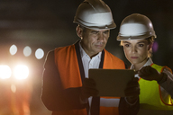 Construction worker and engineer using digital tablet at dark construction site - CAIF10442