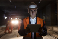 Serious male foreman using digital tablet at dark construction site - CAIF10445