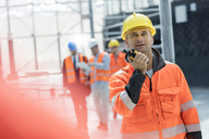 Male foreman using walkie-talkie at construction site - CAIF10448