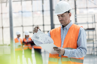 Male engineer reviewing blueprints on clipboard at construction site - CAIF10451