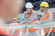 Male foreman and construction worker talking at construction site - CAIF10454