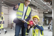 Male foreman and engineer with theodolite at construction site - CAIF10457