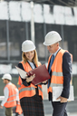 Architects reviewing paperwork at construction site - CAIF10460