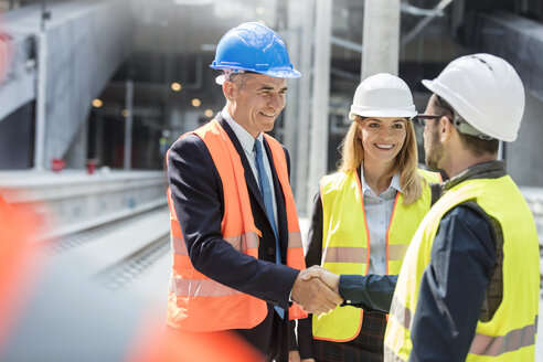 Businessman and engineer handshaking at construction site - CAIF10463