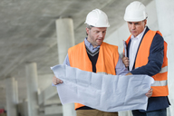 Male engineers examining underground blueprints at construction site - CAIF10469