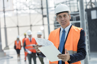 Portrait smiling businessman with clipboard at construction site - CAIF10472