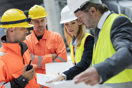 Engineers and construction workers reviewing blueprints at construction site - CAIF10475