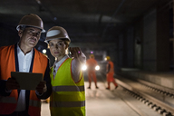 Foreman and engineer with digital tablet talking on dark tracks at underground construction site - CAIF10481