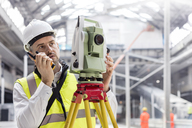 Male engineer using walkie-talkie and theodolite at construction site - CAIF10484