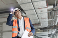 Foreman with flashlight at construction worker - CAIF10487