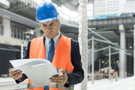 Businessman reviewing paperwork on clipboard at construction site - CAIF10493