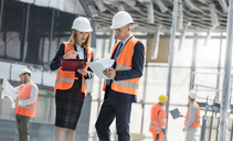 Engineers with clipboards meeting at construction site - CAIF10496