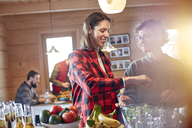 Friends tossing salad in cabin - CAIF10532