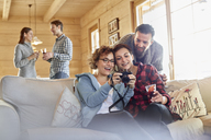 Friends viewing photographs on digital camera on cabin sofa - CAIF10556