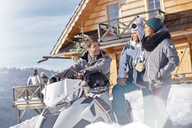 Friends with snowmobile outside sunny cabin - CAIF10568