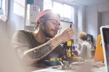 Focused young male designer assembling robotics in workshop - CAIF10598