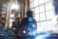 Welder welding with welding mask and torch in workshop - CAIF10601