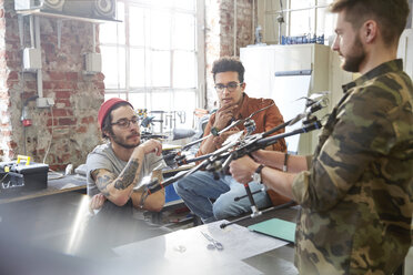 Designers meeting, examining drone in workshop - CAIF10622