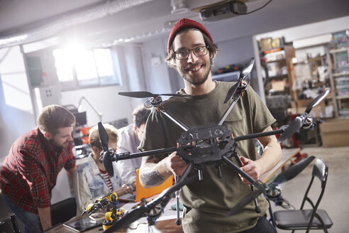 Portrait smiling male designer holding drone in workshop - CAIF10625
