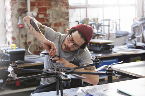 Male designer with tattoos assembling drone in workshop - CAIF10631