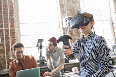 Female designer texting virtual reality simulator glasses and using joystick in workshop - CAIF10634