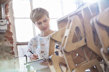 Female designer examining prototype and taking notes - CAIF10646