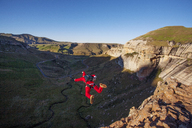 Rear view of man with parachute BASE jumping from cliff - CAVF05199