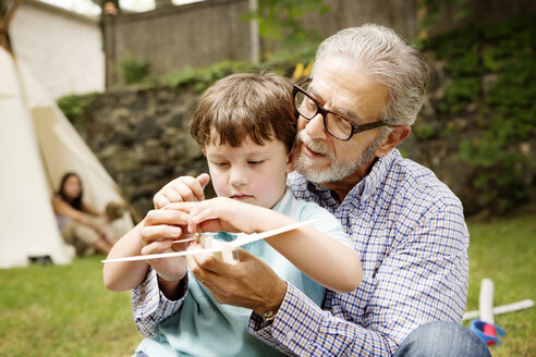 Boy playing with grandfather in lawn - CAVF05433