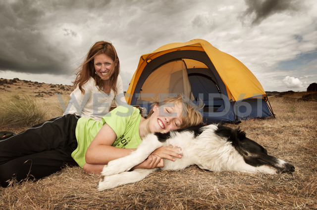 Mother looking at son lying with dog on field - CAVF05502 - Cavan Images/Westend61