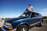 Man looking away while sitting on car against blue sky - CAVF05508