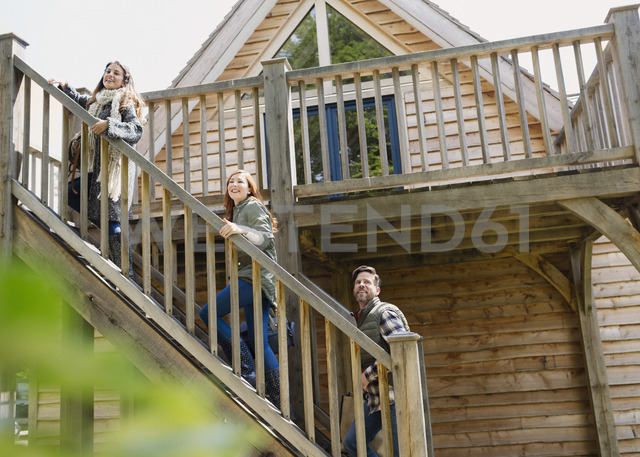 Friends climbing staircase outside wooden cabin - CAIF10697