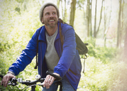 Smiling man mountain biking in woods - CAIF10700