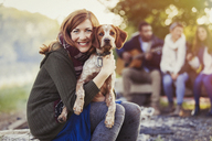 Portrait smiling woman hugging dog at campsite with friends - CAIF10712