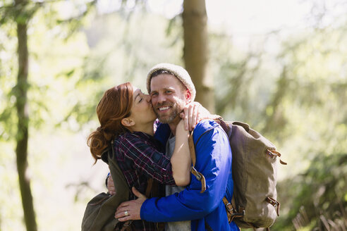 Portrait smiling couple kissing hiking in woods - CAIF10718