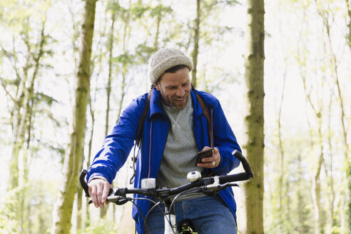 Man mountain biking texting with cell phone in woods - CAIF10721