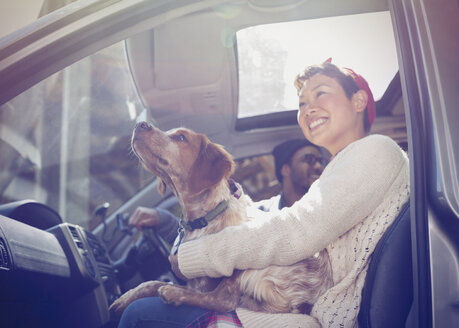 Smiling woman holding dog on lap in car - CAIF10730