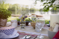 Place settings and simple bouquet on garden party table at lakeside - CAIF10742