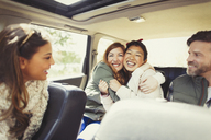 Enthusiastic female friends hugging in back seat of car - CAIF10745
