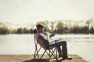 Man drinking coffee and using digital tablet on sunny lakeside dock - CAIF10751