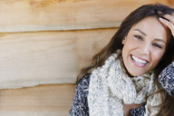 Portrait smiling brunette woman with scarf and hand in hair - CAIF10754