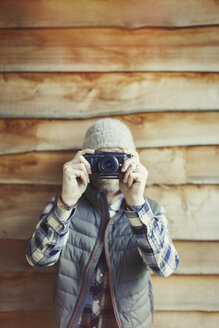 Portrait man using camera outside cabin - CAIF10766