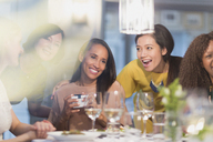 Smiling women friends celebrating birthday at restaurant table - CAIF10769