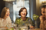 Laughing women friends dining and talking at restaurant table - CAIF10772