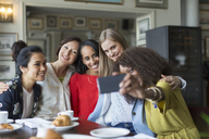Smiling women friends taking selfie at restaurant table - CAIF10775